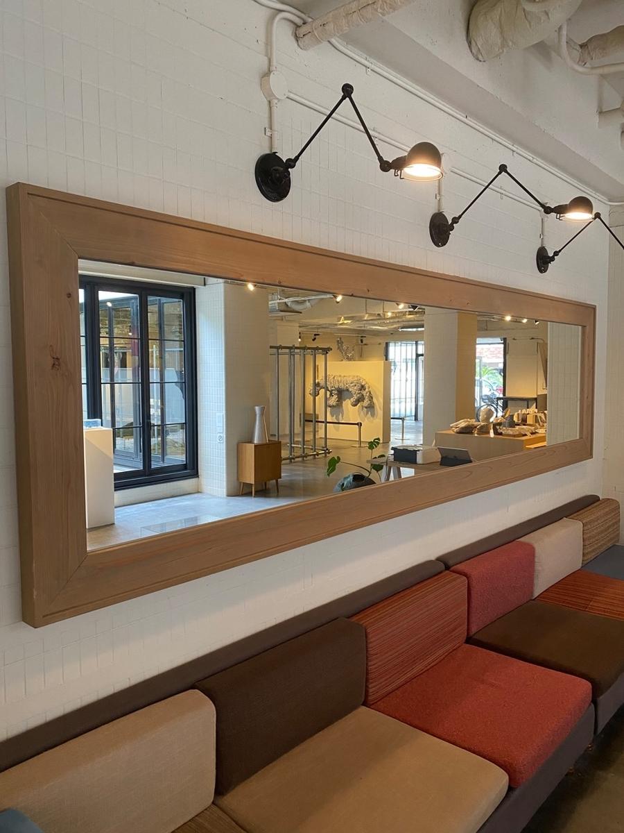 写真_ソファーの上にある横に長い鏡にロビーに展示されている作品が映っている