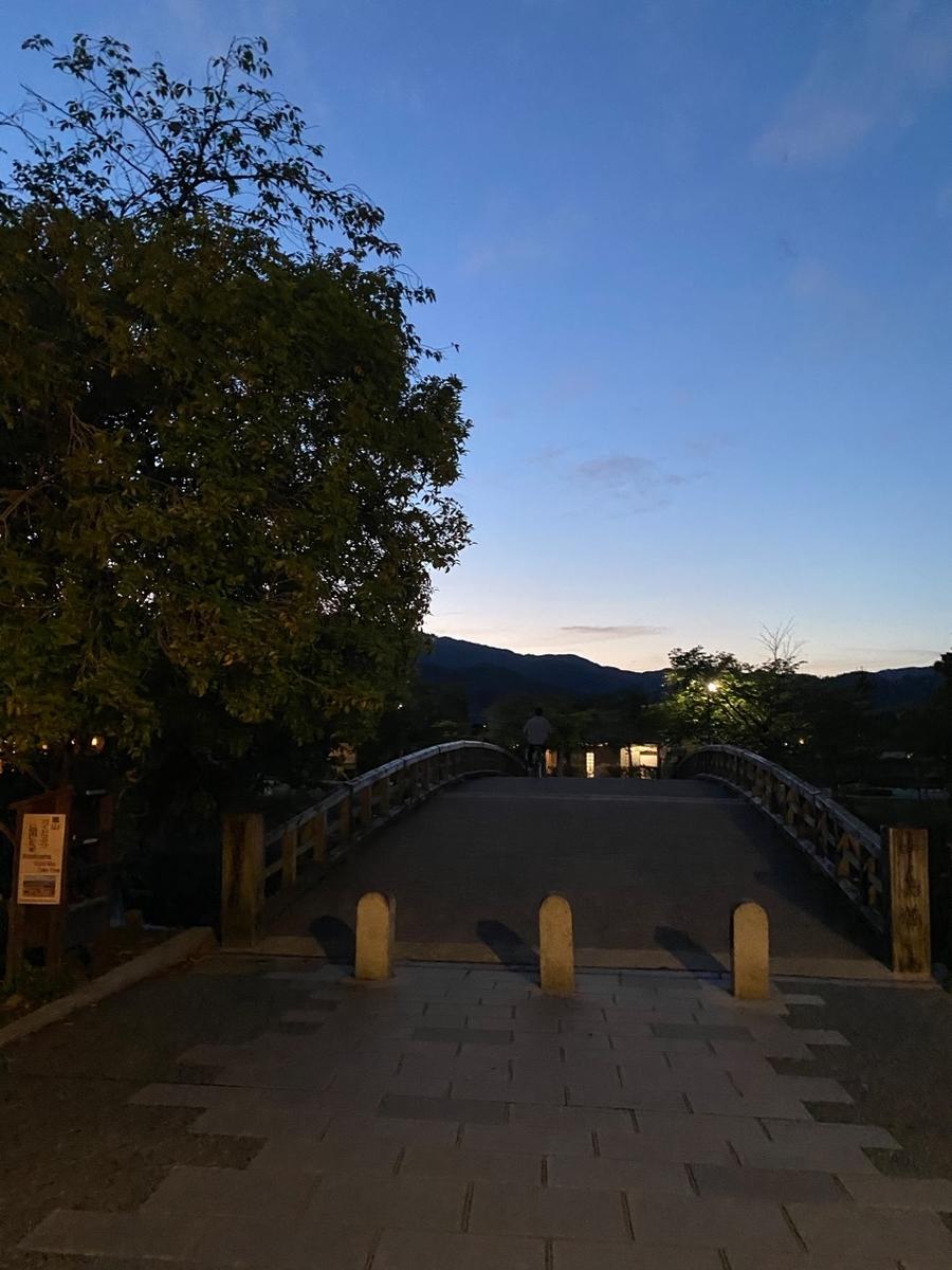 写真_夜空と橋と木があり、橋の手前に石がある