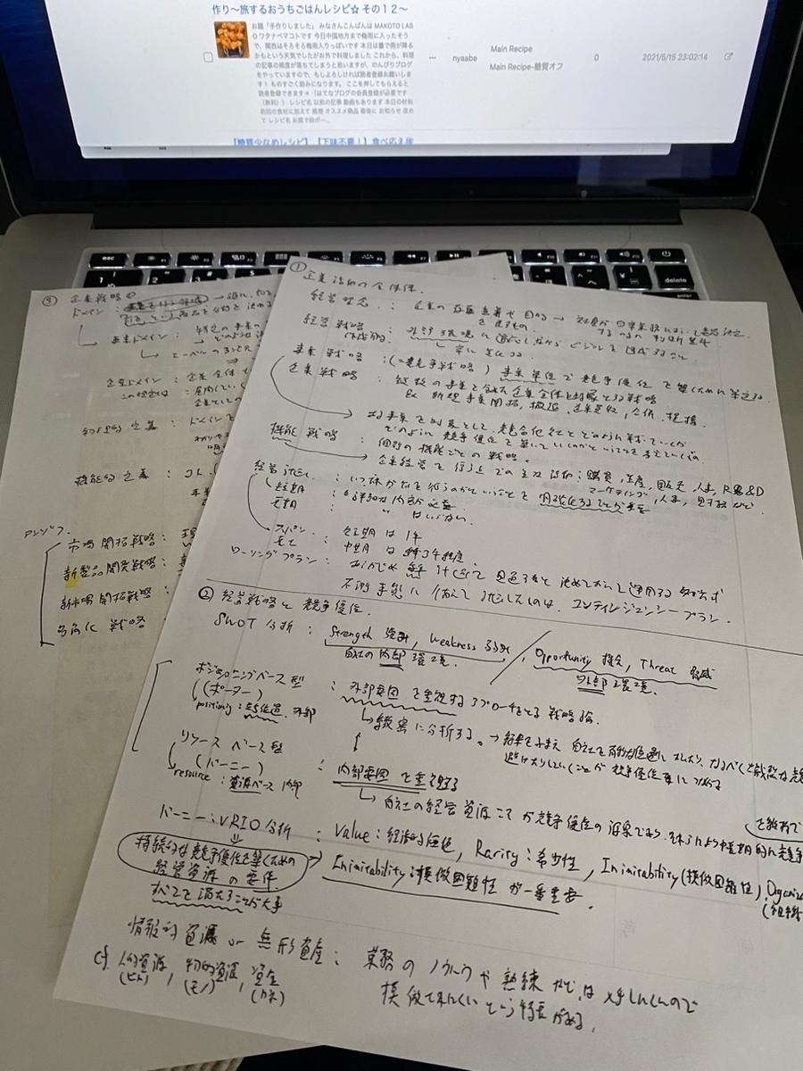 写真_パソコンのて手前に文字が書かれた紙が二枚ある