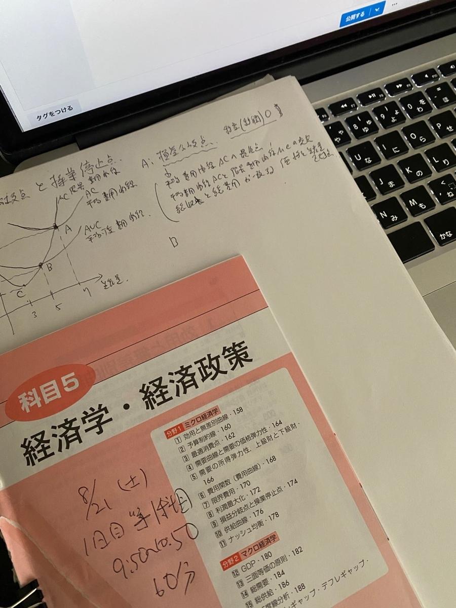 写真_パソコンの画面手前に、経済学・経済政策と描かれた冊子と紙がある