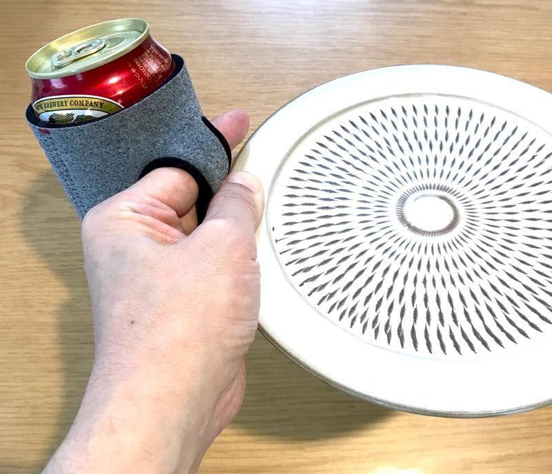「通せるクージー」で缶ビールとお皿を片手で持つ図