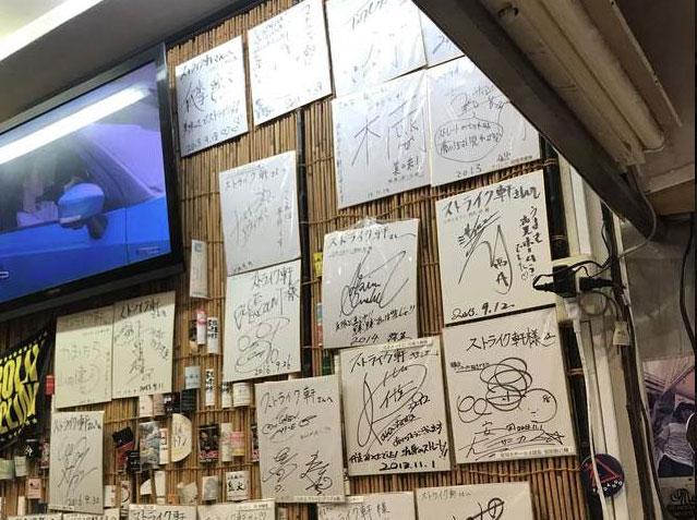 テレビと壁に飾られたたくさんのサイン色紙