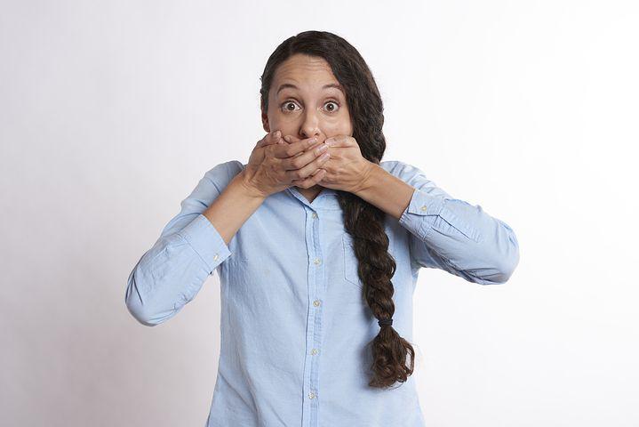口臭を隠すしぐさの女の人