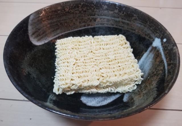 インスタントラーメンの麺を器に入れる