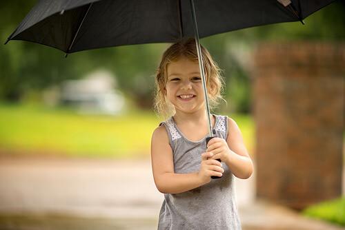 傘をさして笑う女の子