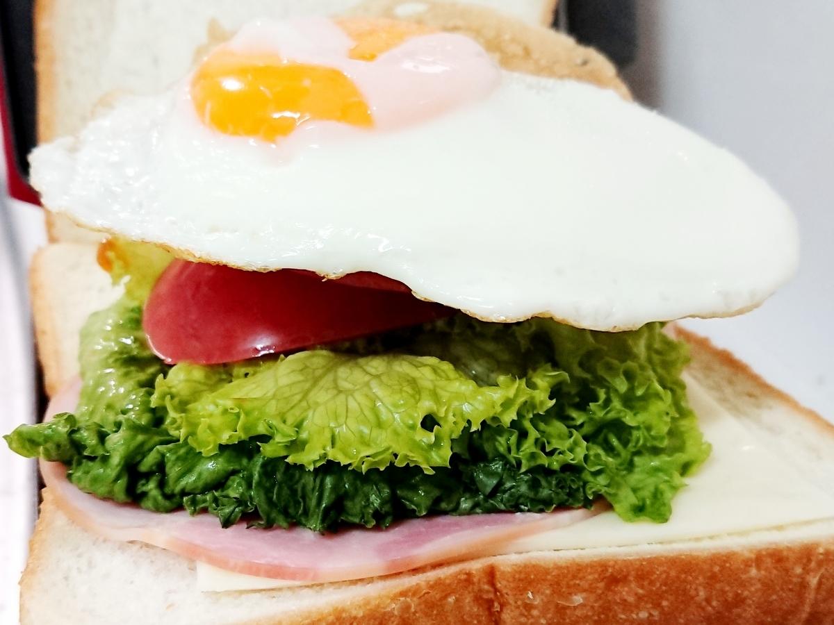 トマトレタスハム卵が挟まったサンドイッチ