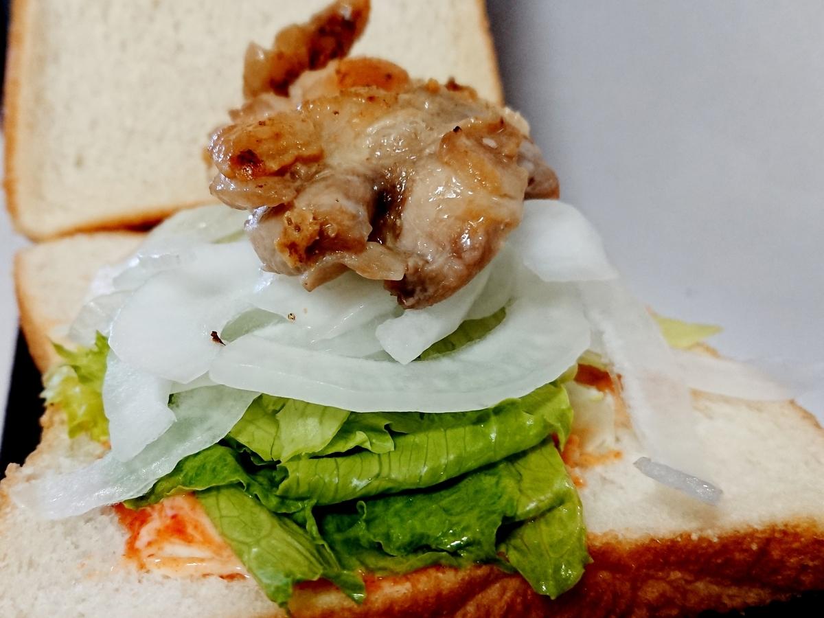パンの上にレタス、玉ねぎ、鶏肉