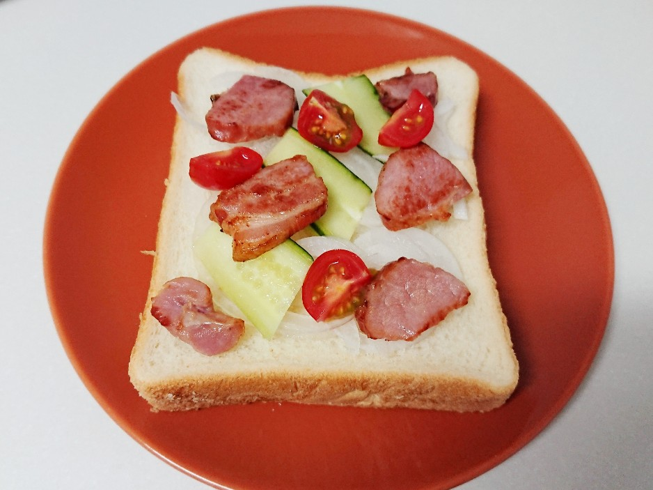 食パンの上に玉ねぎ、きゅうり、ベーコン、トマト