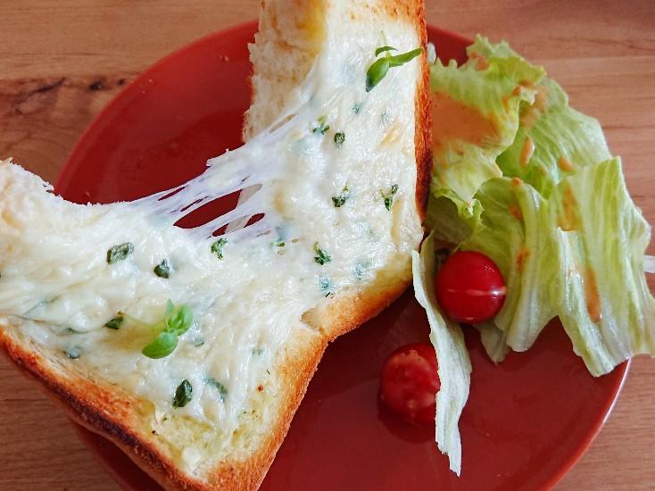 バジルチーズトーストを半分に割っている