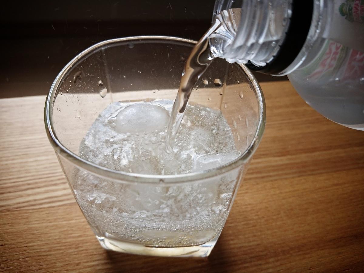 グラスに炭酸水を注いでいる