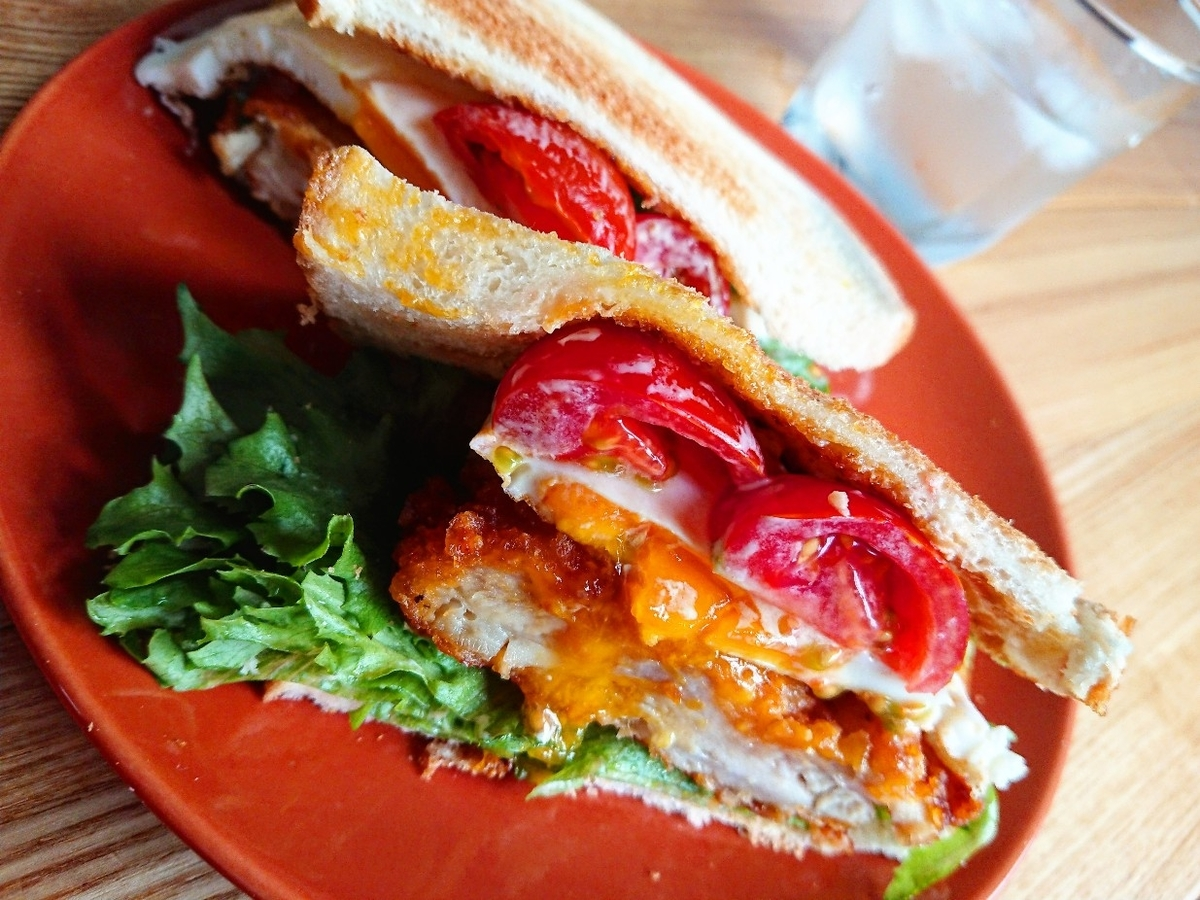 フライドチキン 目玉焼き 野菜が挟まったサンドイッチ