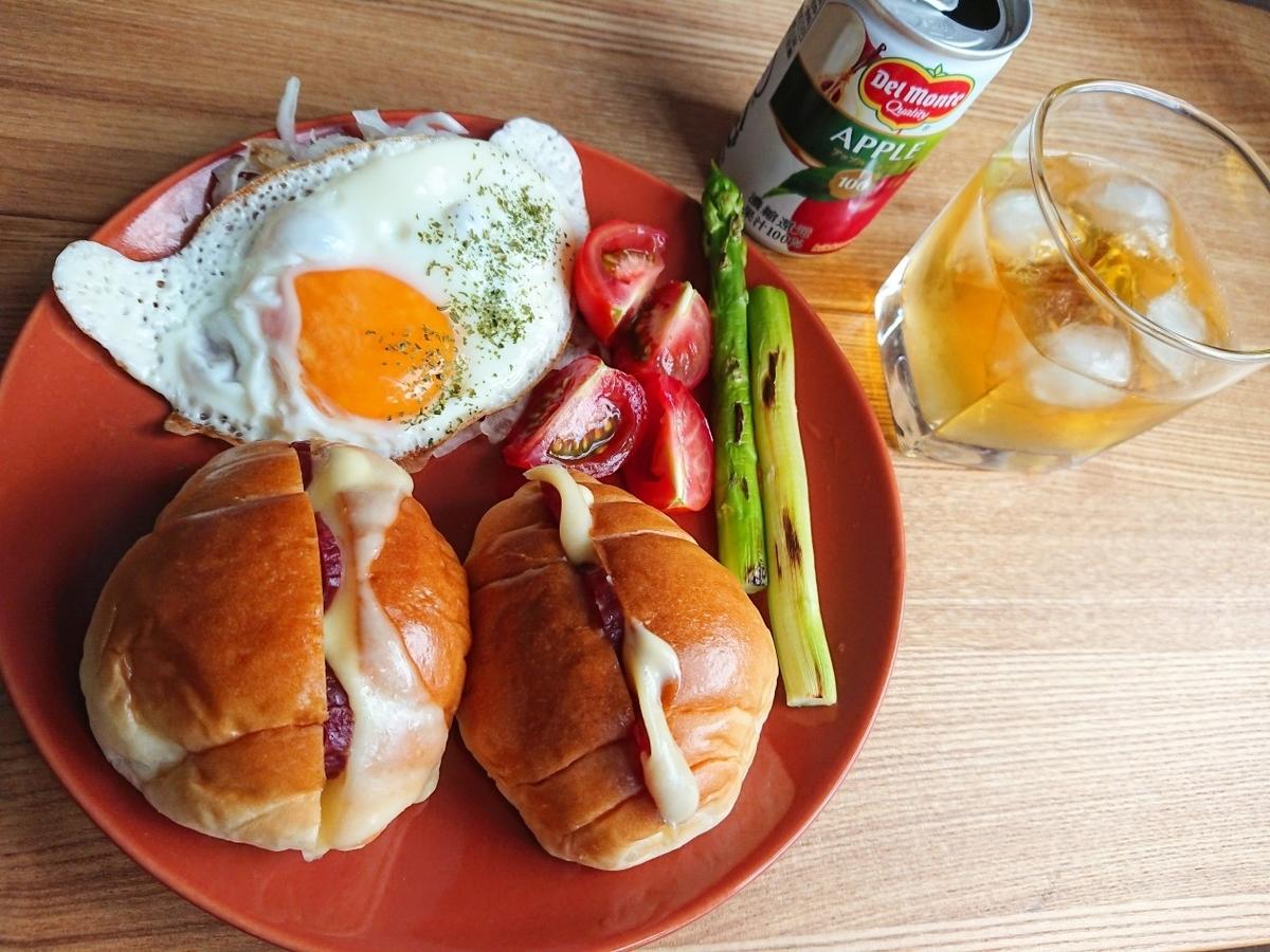 チーズが挟まったロールパン 目玉焼き アスパラガス トマト ジュース