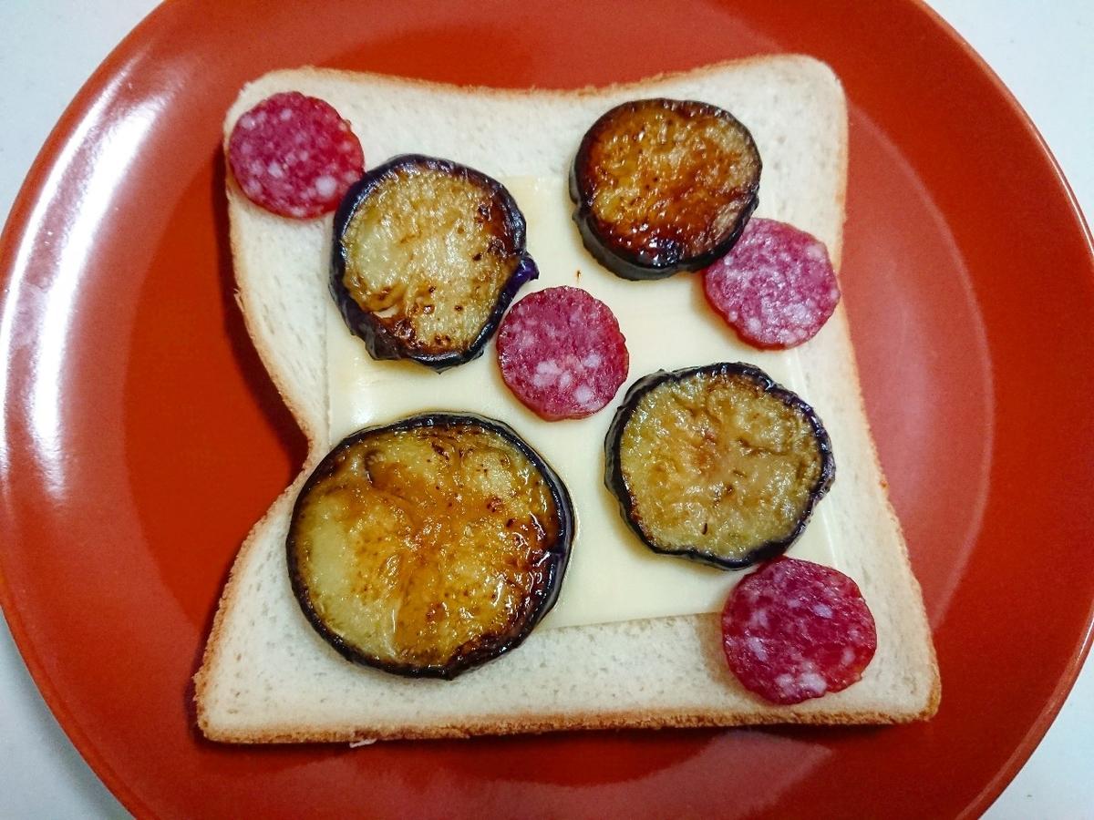 食パンの上にチーズと茄子とカルパスをのせている