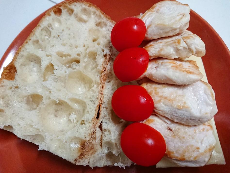 バゲットの上にチーズ、鶏肉、トマト