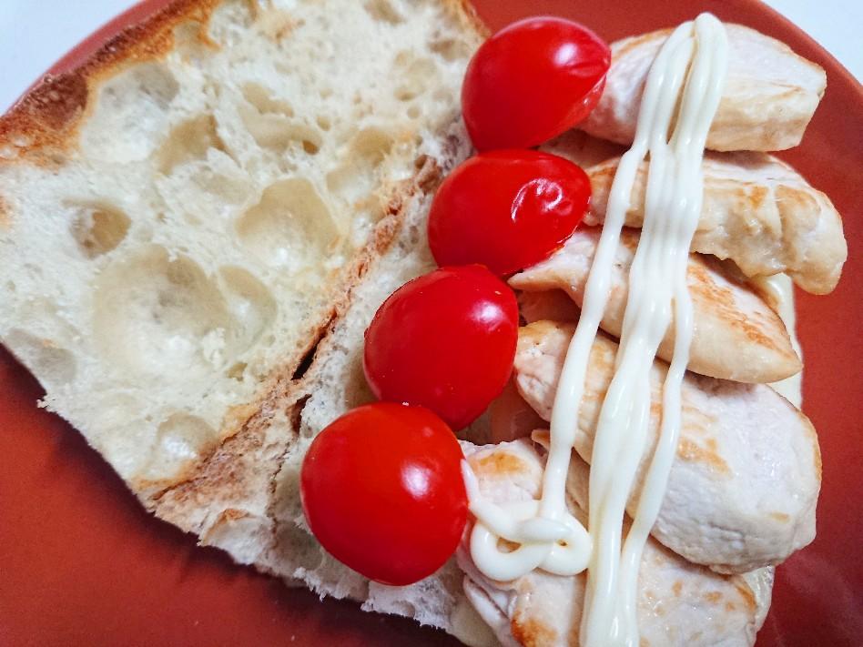 パンの上に鶏肉とトマトがのっている