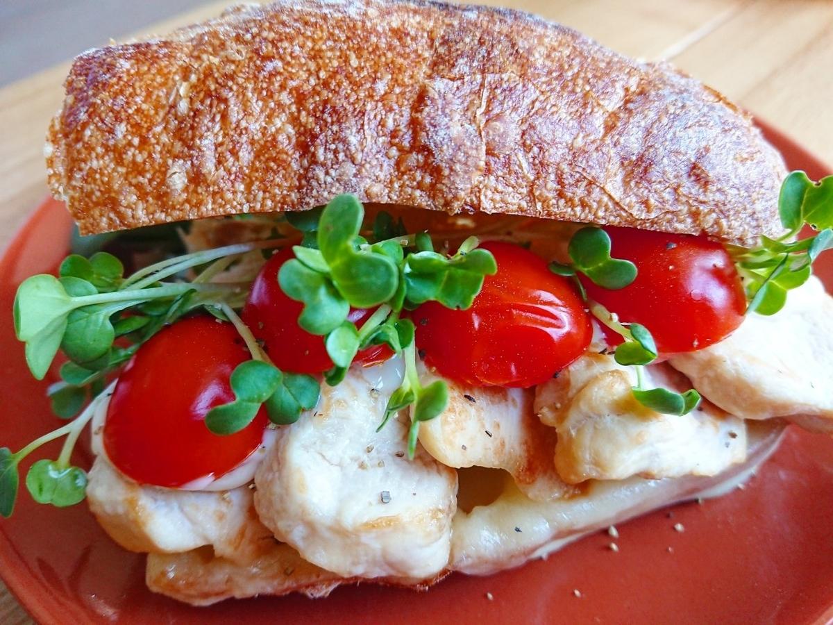 鶏肉、トマト、チーズが挟まったサンドイッチ