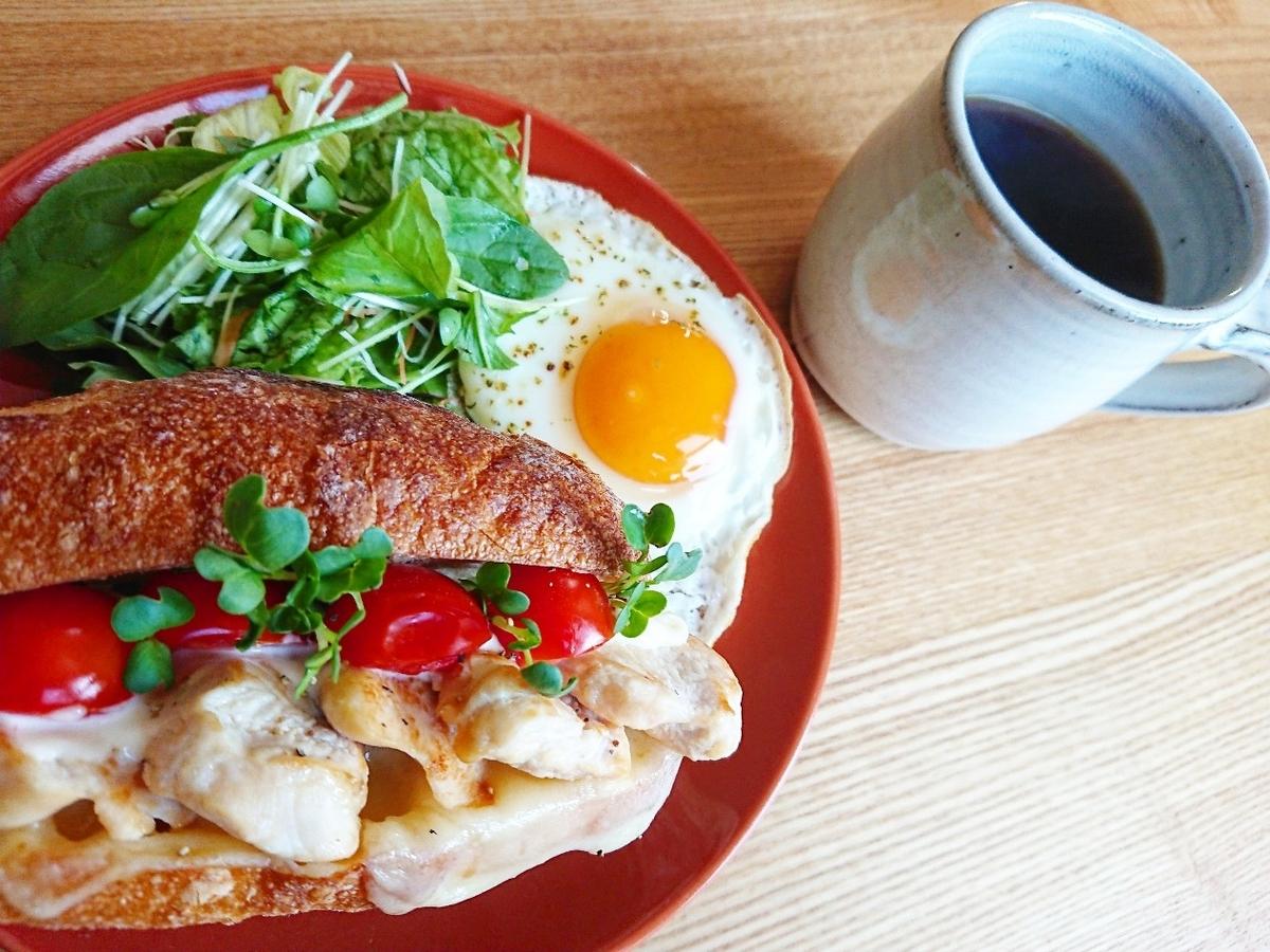 鶏肉とトマトが挟まったサンドイッチ 目玉焼き サラダ コーヒー