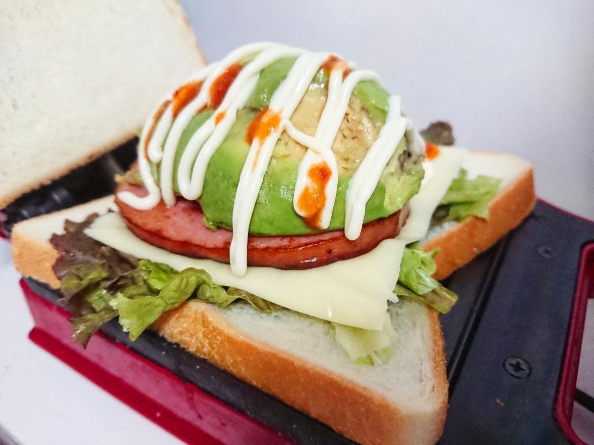 食パンの上にレタス、チーズ、ソーセージ、アボカド