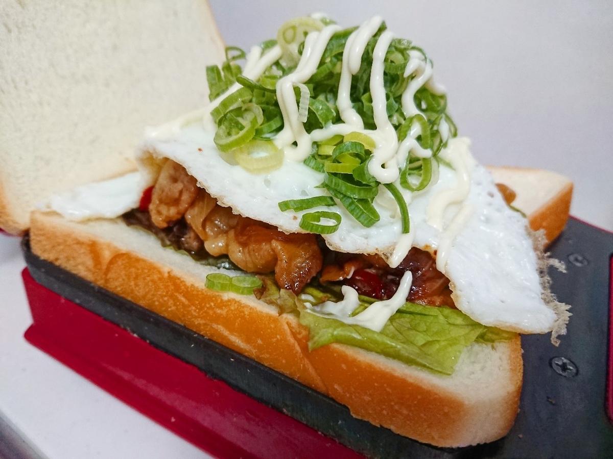食パンの上に豚肉、目玉焼き、ネギをのせている