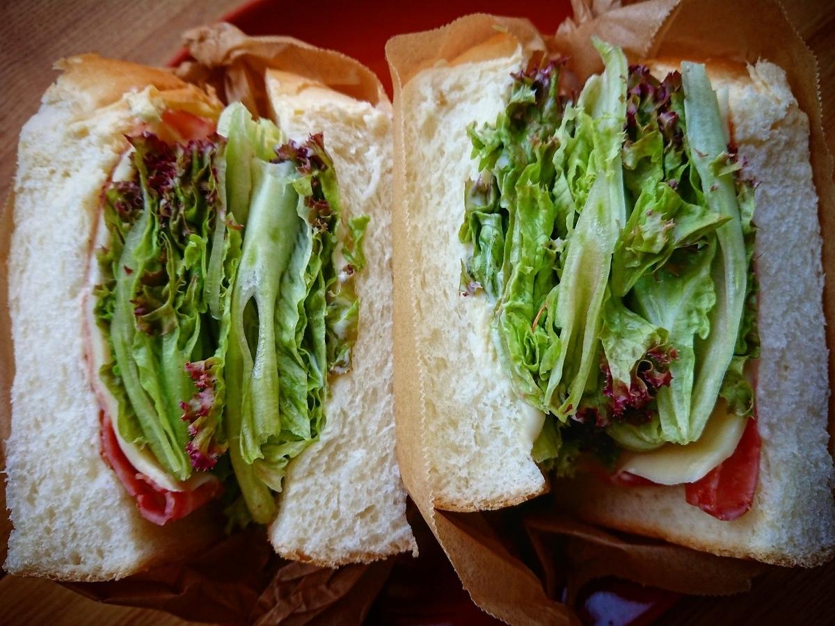 ハムとレタスが挟まった分厚いサンドイッチ