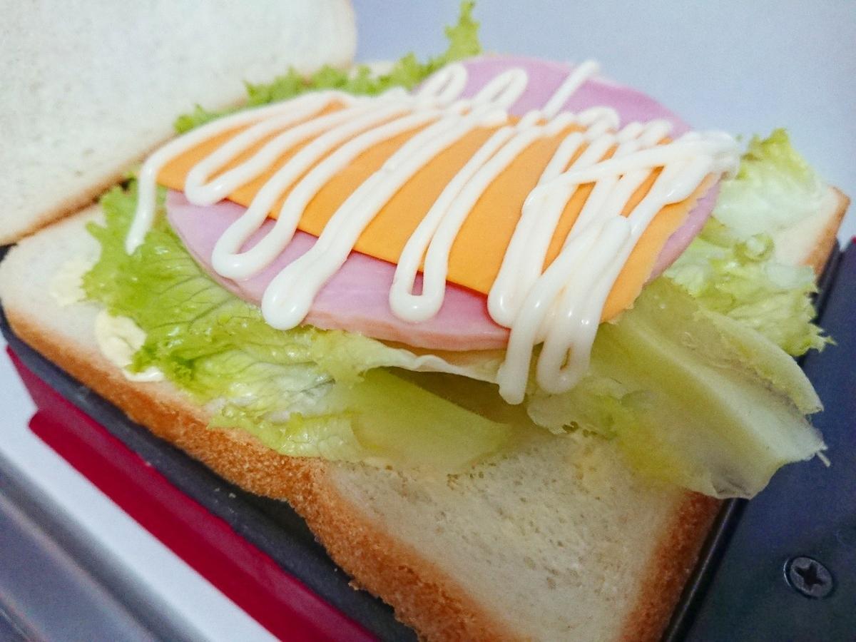 食パンの上にレタス、ハム、チェダーチーズ、マヨネーズがのっている