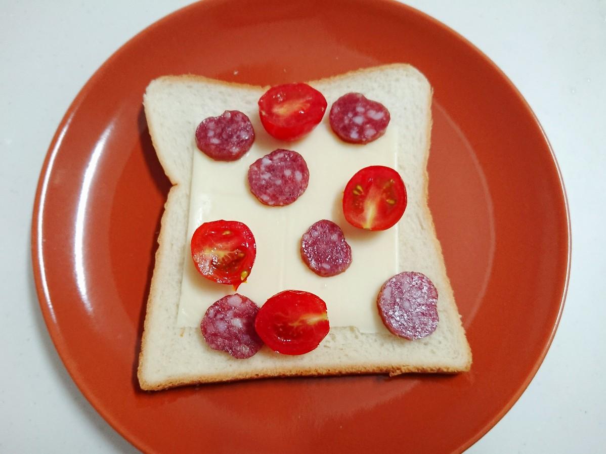 食パンの上にチーズ、カルパス、トマト