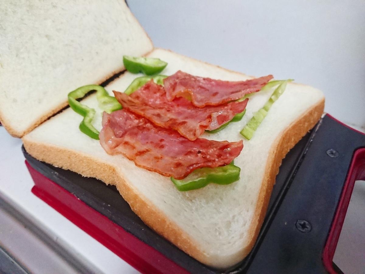 食パンの上にピーマンとベーコン