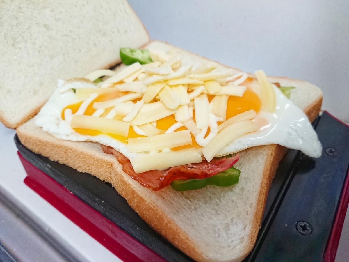 食パンの上にピーマン、ベーコン、目玉焼き、チーズがのっている