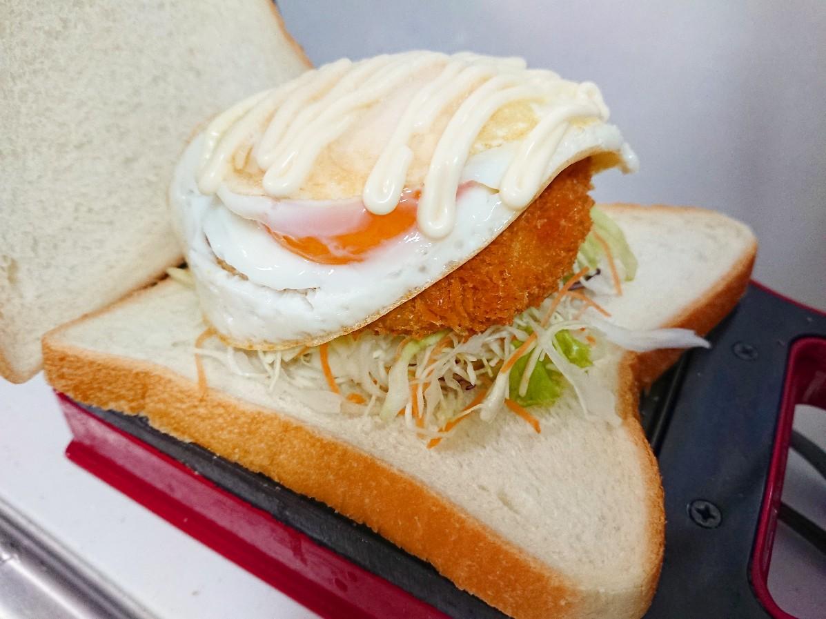 食パンの上に野菜、コロッケ、目玉焼き