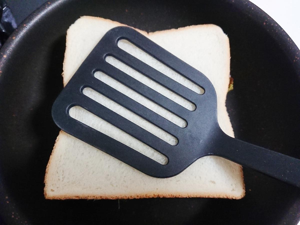 フライパンで焼いている食パンをフライ返しで押さえている