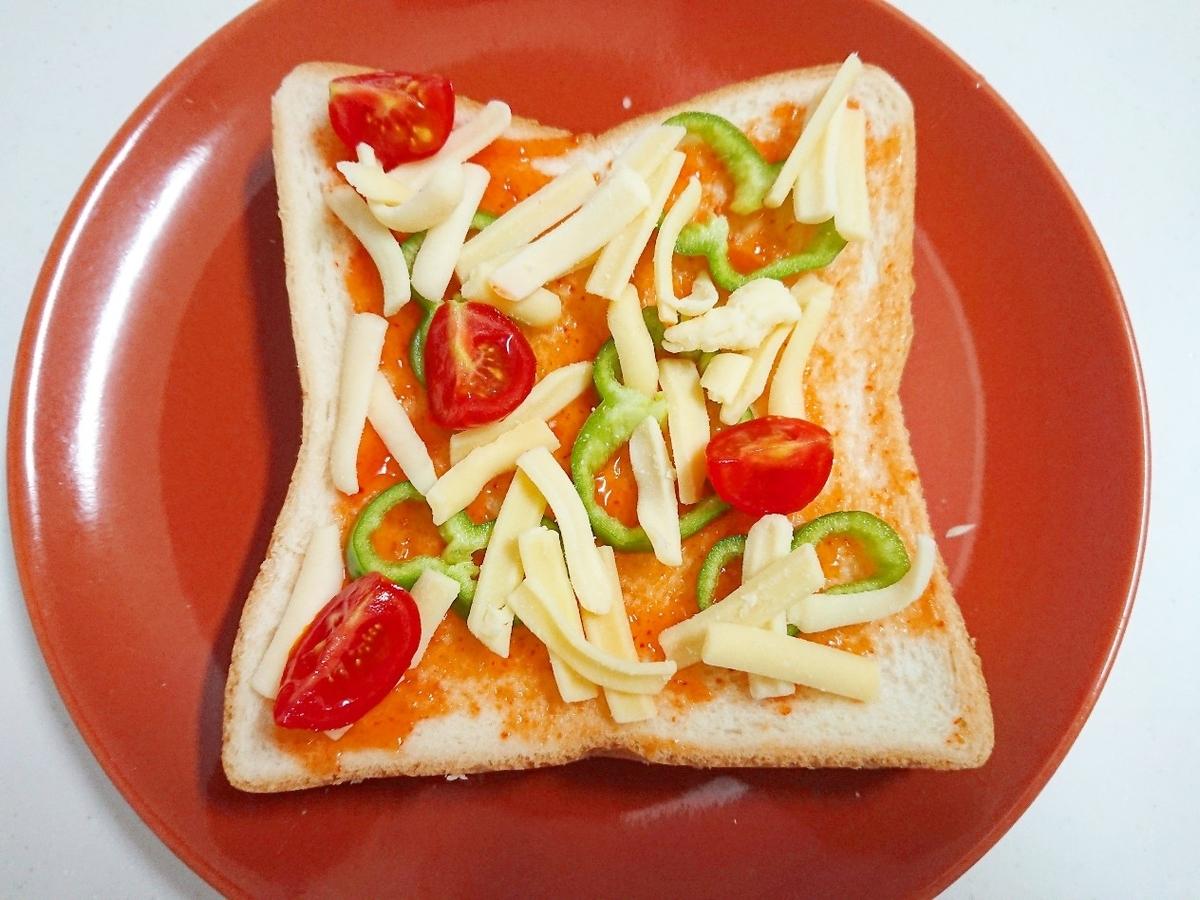 食パンの上にチーズ、トマト、ピーマンがのっている