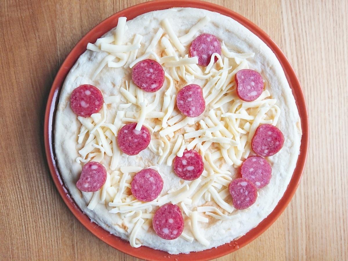 ピザ生地の上にカルパスとチーズ