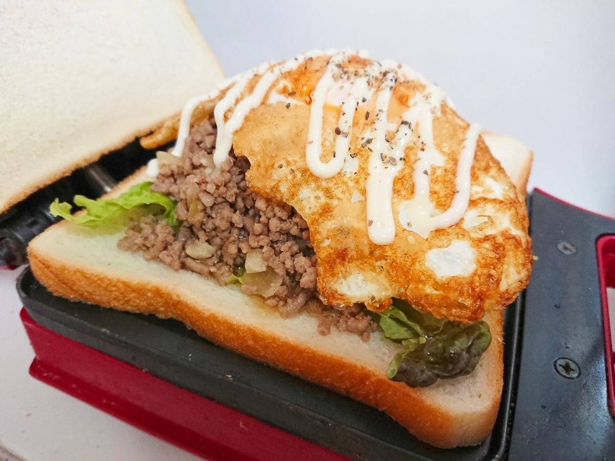食パンの上にたっぷりのひき肉と目玉焼き