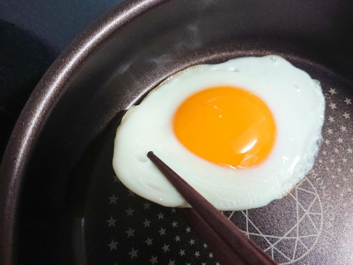 フライパンで焼いた卵を箸で持ち上げている