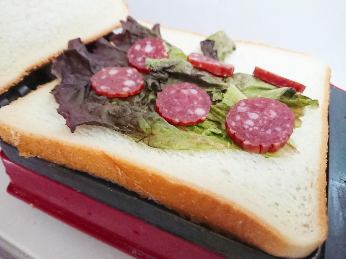 食パンの上にレタスとサラミをのせている