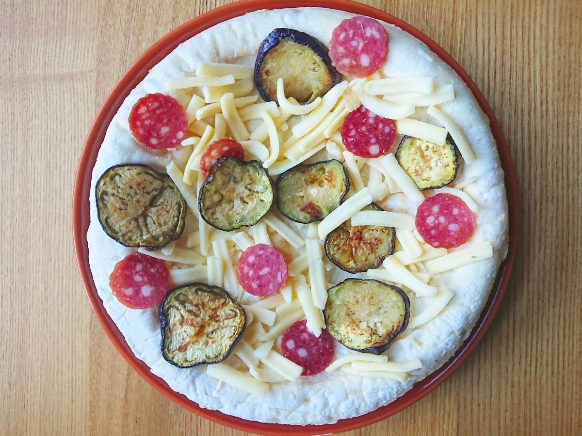 ピザ生地の上に茄子とサラミとチーズがのっている