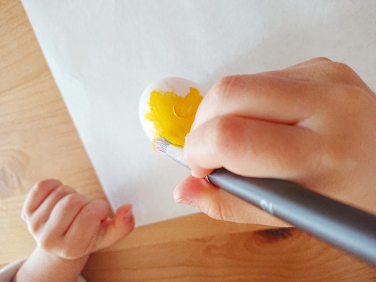 子供が卵に色を塗っている
