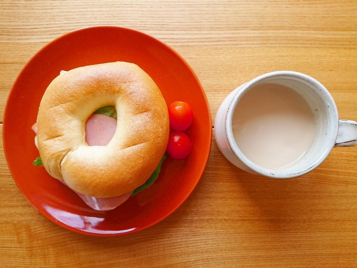 ハム、チーズ、レタスが挟まったベーグル コーヒー牛乳