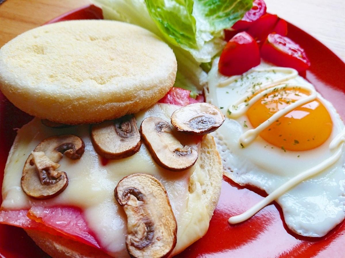 ベーコン、チーズ、マッシュルームが挟まったマフィン 目玉焼き サラダ