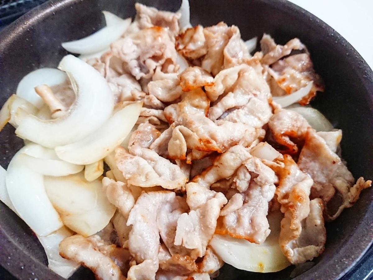 豚バラと玉ねぎを炒めている