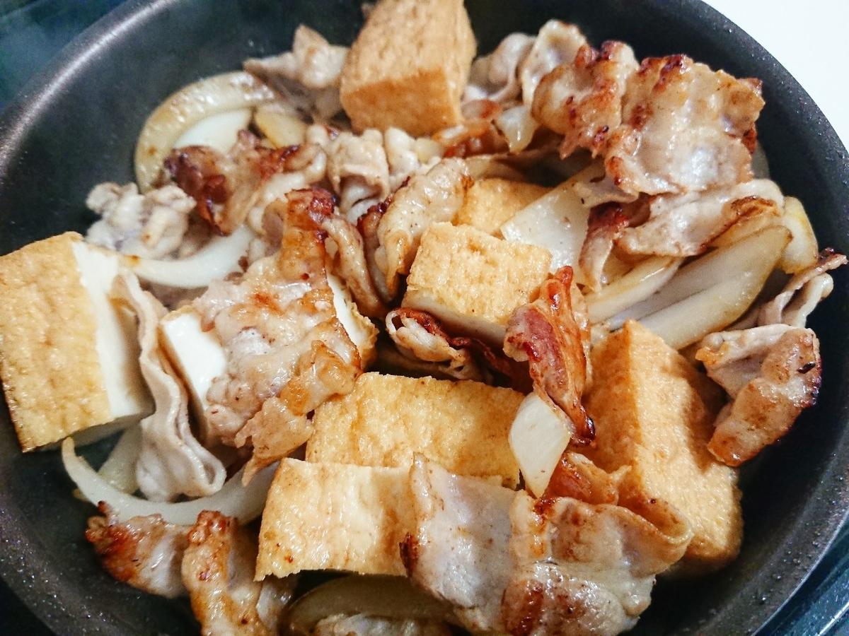 豚バラと玉ねぎと絹厚揚げを炒めている