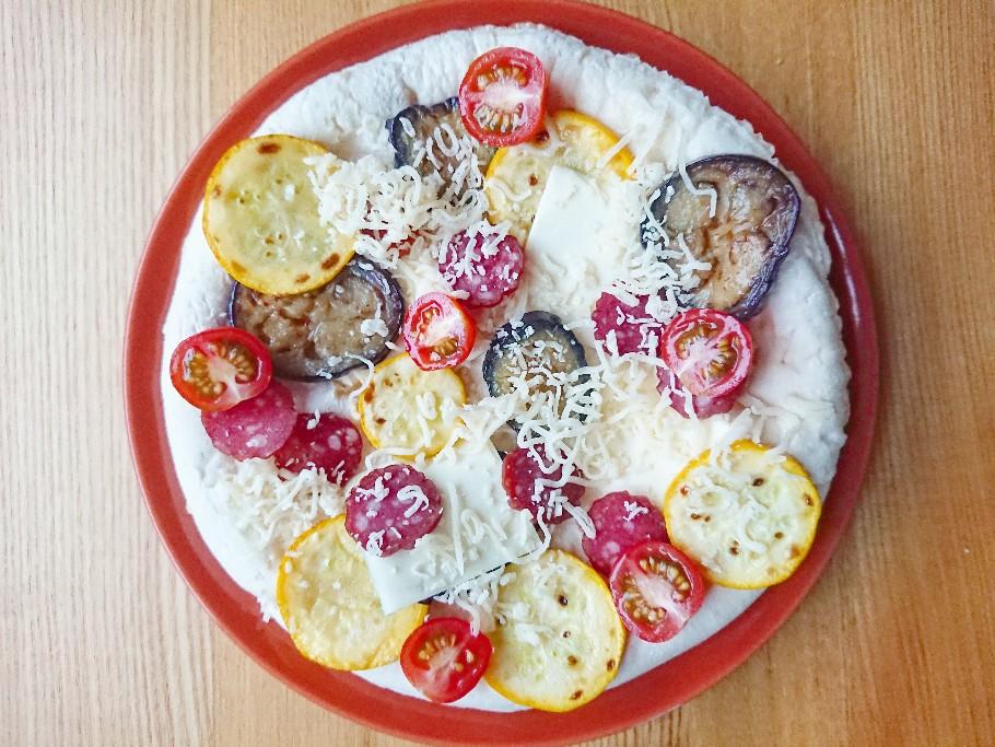 ピザ生地の上に夏野菜とサラミとチーズがのっている