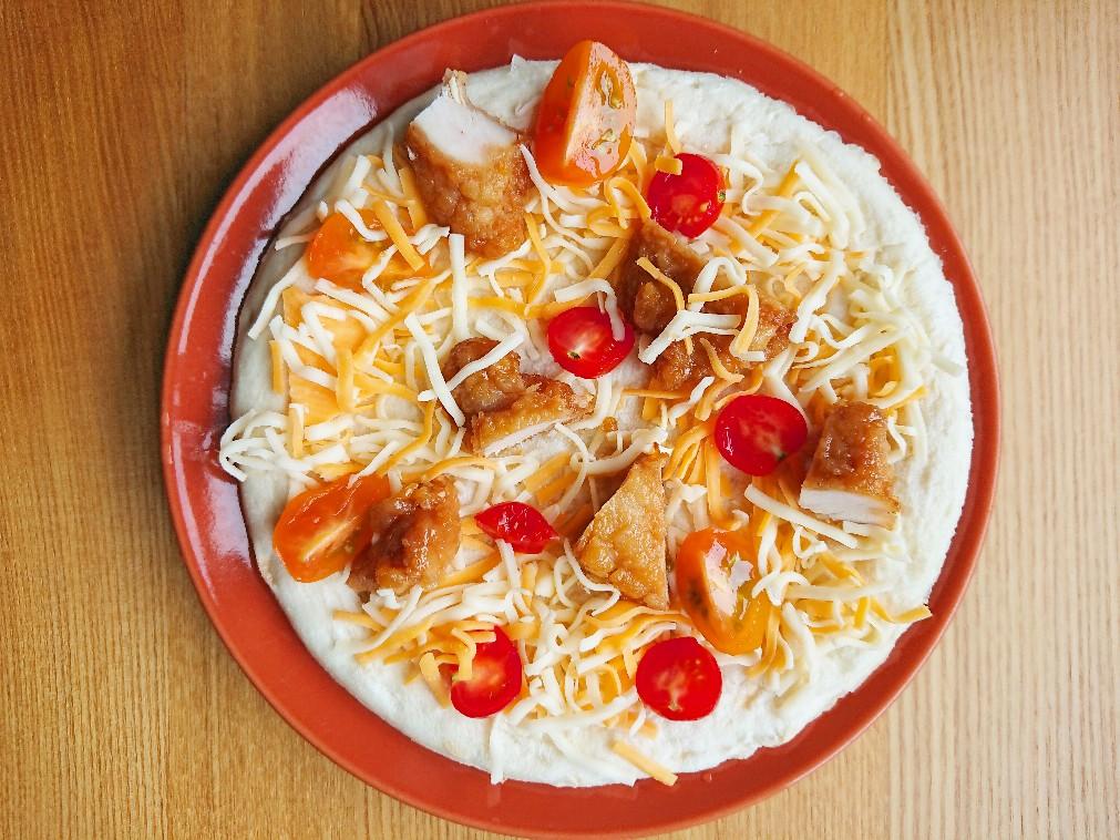 唐揚げ、チーズ、トマトがのったピザ生地