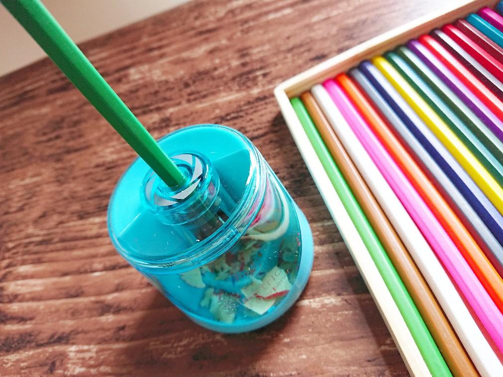 電動鉛筆削りに色鉛筆を挿している