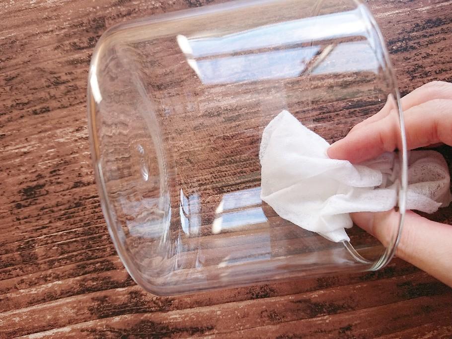 ガラス容器を布で拭いている