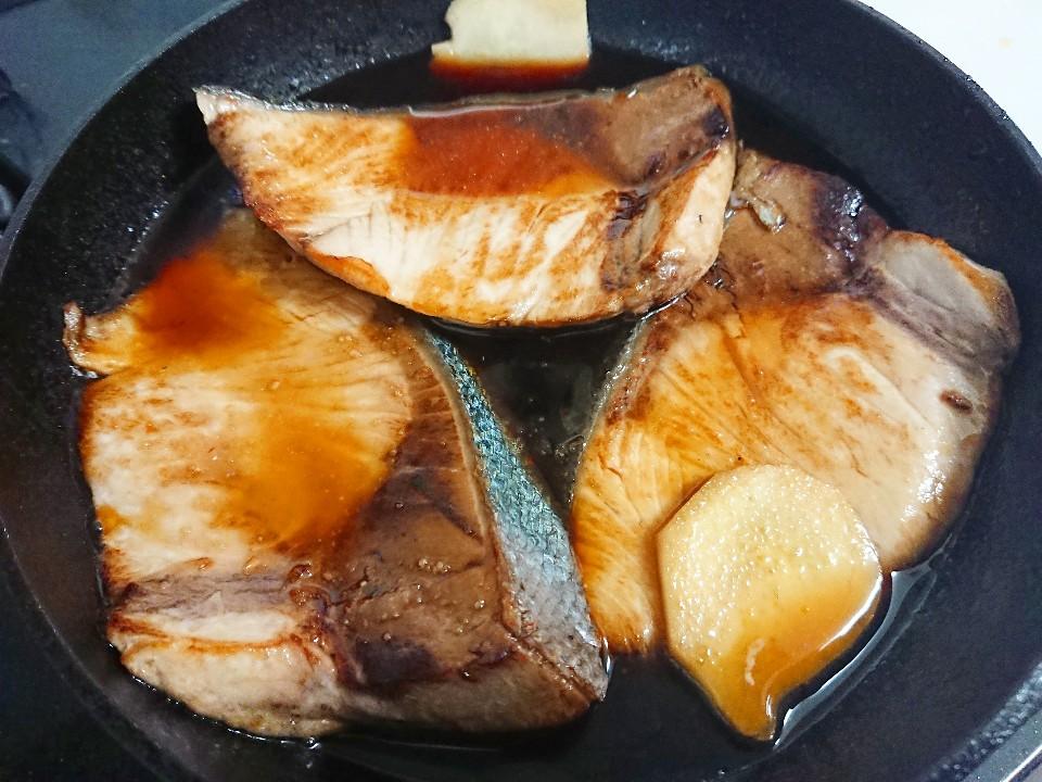 フライパンでブリを煮ている