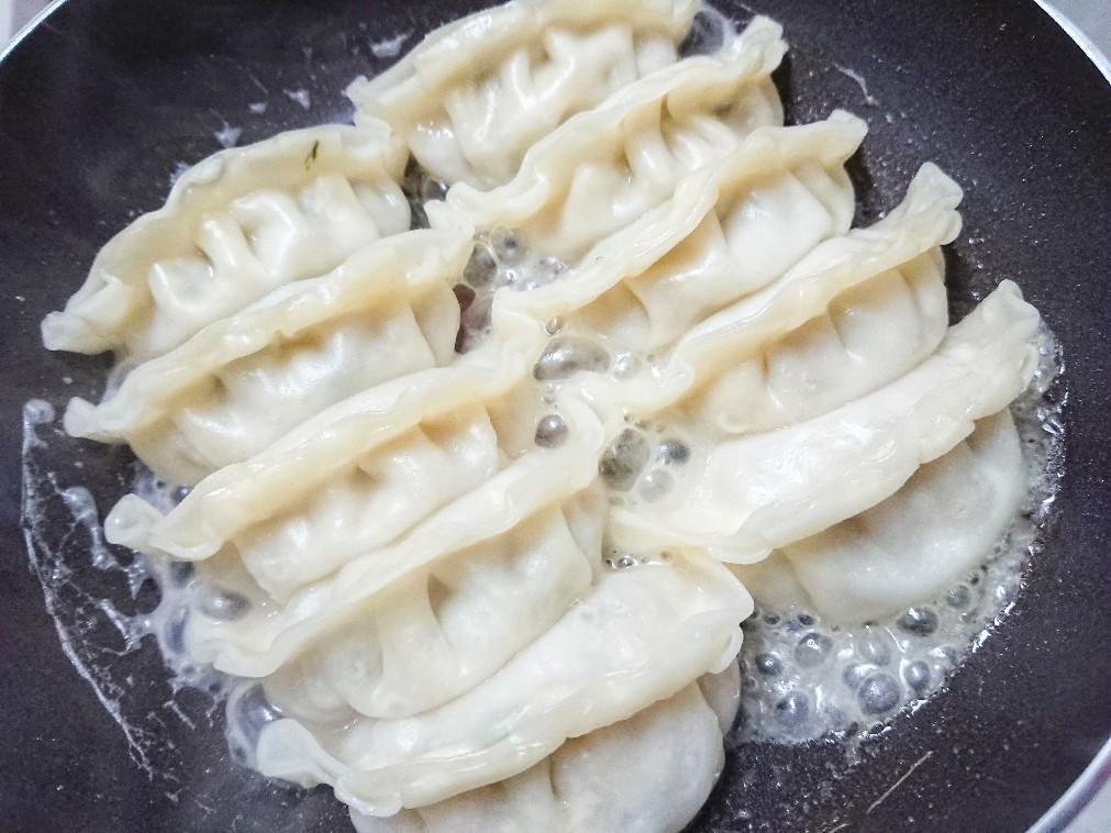フライパンで餃子を焼いている