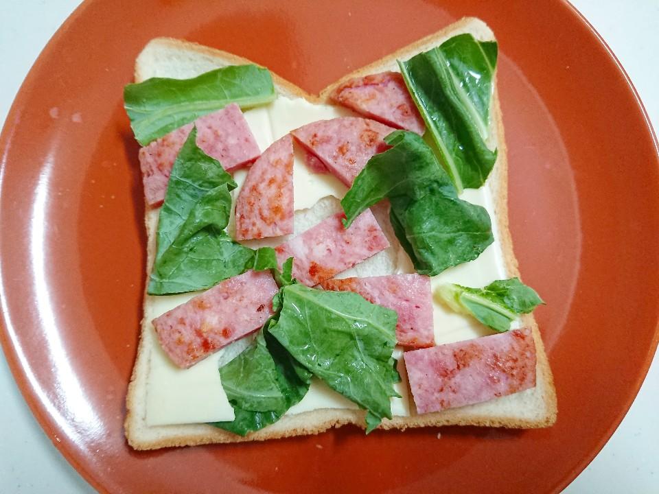 食パンの上にチーズとソーセージとケール