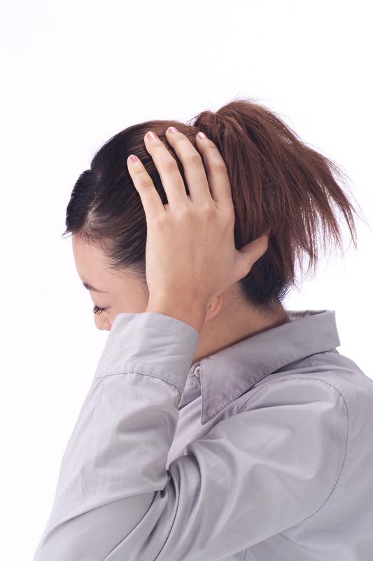 緊張性頭痛の女性