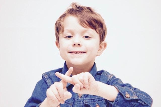 こちらを向いてバッテンマークを作るジージャンを着た可愛い少年